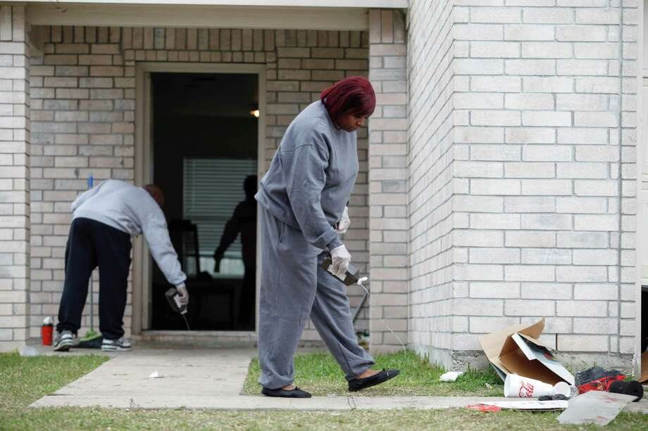 Tonya Grice uses hydrogen peroxide to clean the blood from the walkway of her sister's Cypress-area house, where two teenagers were killed and about 20 more wounded late Saturday when gunfire erupted at an 18-year-old's birthday party. Photo: Eric Kayne / Eric Kayne