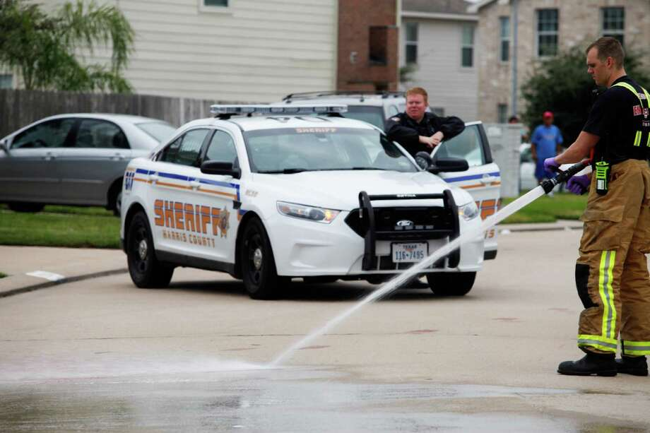 Firemen wash away a pool of blood down the street from where two people were killed and at least 16 others wounded late Saturday when gunfire erupted at a house party in the Cypress area, authorities said. The shooting broke out about 11:15 p.m. in the 7300 block of Enchanted Creek Drive, near Fry and FM 529. Nov. 10, 2013 in Houston. Photo: Eric Kayne, For The Chronicle / Eric Kayne