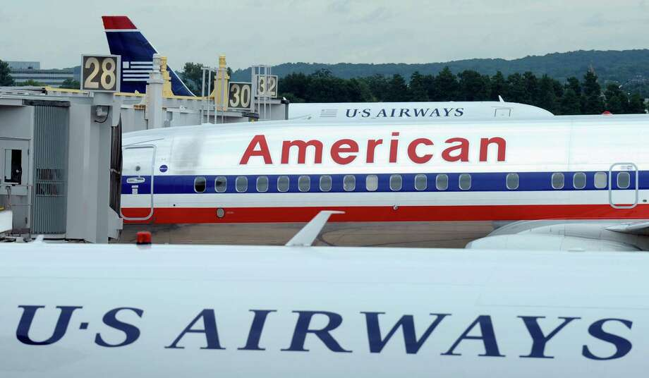 An American Airlines plane is seen between two US Airways planes at Washington's Ronald Reagan National Airport, Tuesday, Aug. 13, 2013. Photo: Susan Walsh