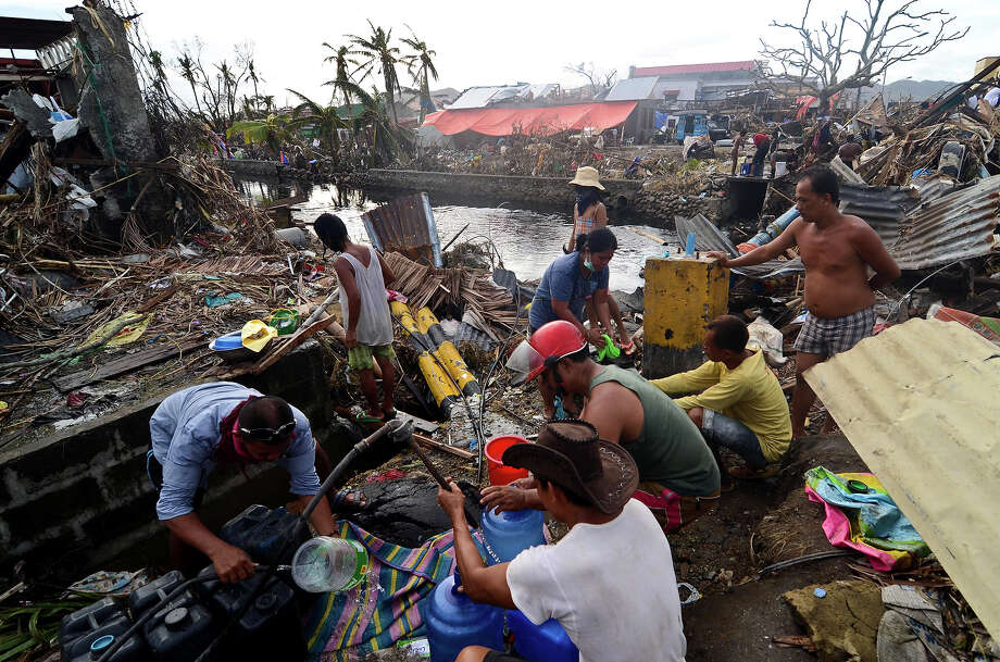 Survivors collect water from a broken water pipe in an area devastated by Typhoon Haiyan on November 12, 2013 in Leyte, Philippines. Four days after the Typhoon Haiyan devastated the region many have nothing left, they are without food or power and most lost their homes. Around 10,000 people are feared dead in the strongest typhoon to hit the Philippines this year. Photo: Dondi Tawatao, Getty Images / 2013 Getty Images
