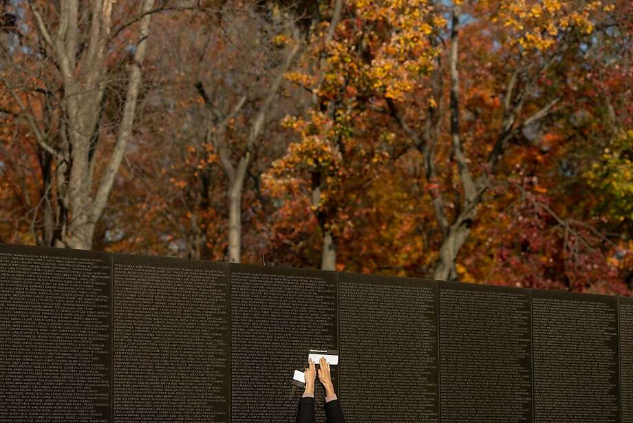 Marble memorial: A visitor makes a rubbing of a name on the Vietnam Veterans Memorial on Veterans Day in Washington. Photo: Chip Somodevilla, Getty Images