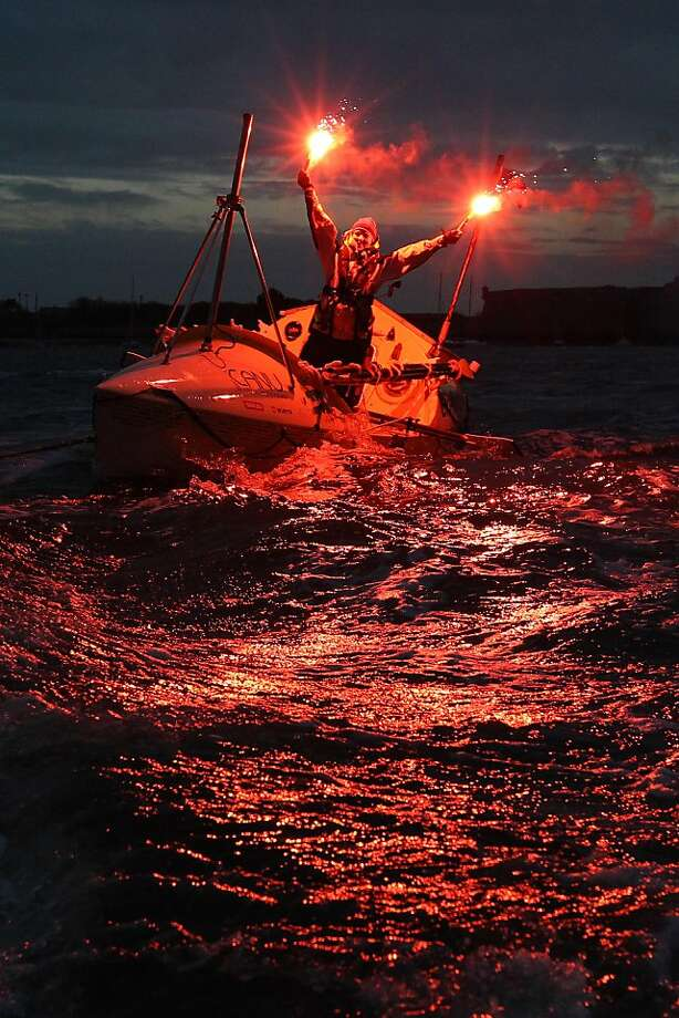 A long row across the pond: Quebec rower Mylene Paquette waves flares in celebration as she arrives in Lorient, 