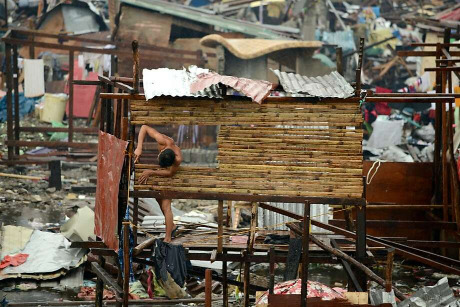 A man rebuildsa shantytown house leveled by Super Typhoon Haiyan in Tacloban, Philippines. Photo: Noel Celis, AFP/Getty Images