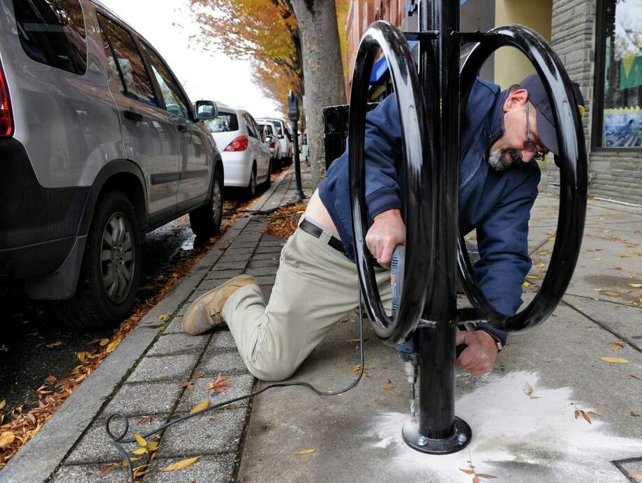 Robert Ambrose, an employee with the Danbury Parking Authority, installs one of four bicycle racks in the downtown area Tuesday, Nov. 12, 2013. Photo: Carol Kaliff / The News-Times