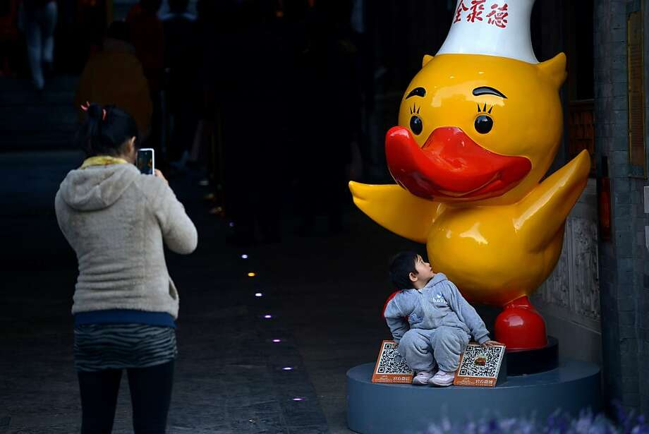 Don't forget to duckwhen you stand up after she takes your picture, young man. You could quack your skull. (Beijing.) Photo: Wang Zhao, AFP/Getty Images