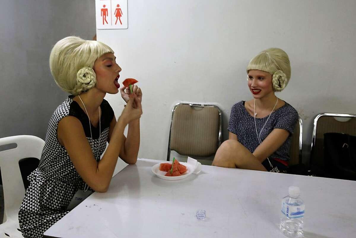 One night in Bangkok: Big-wigged Russian models enjoy watermelon backstage before an evening show at Bangkok International Fashion Week.