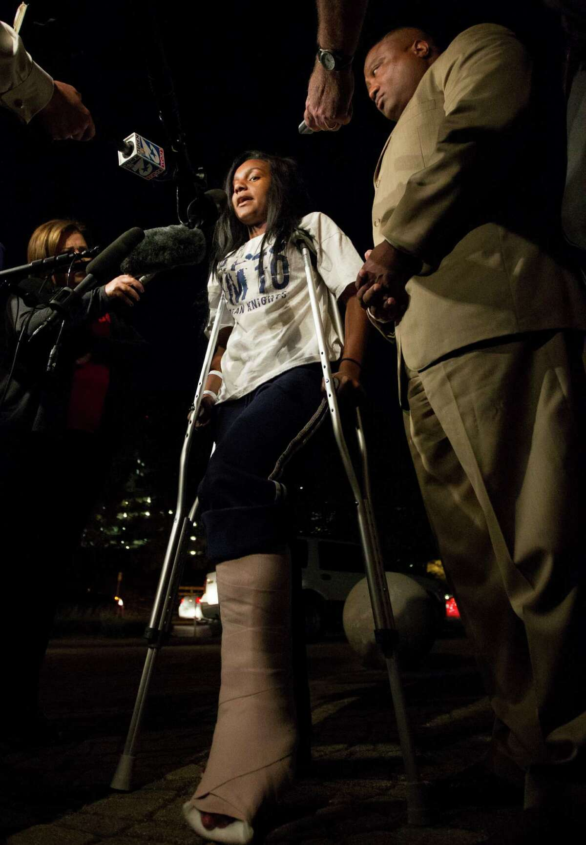 Quanell X stands with Brayiannia Young during a press conference outside Ben Taub hospital on Monday, Nov. 11, 2013, in Houston. Brayiannia was shot during a house party where two people were killed and 19 injured in the Cypress area on Saturday night. Her brother, Willie Young, 21, was arrested and charged with deadly conduct on Monday. A second suspect Randy Stewart, 18, was arrested and charged with aggravated assault. She claims her brother could not have done the shooting.