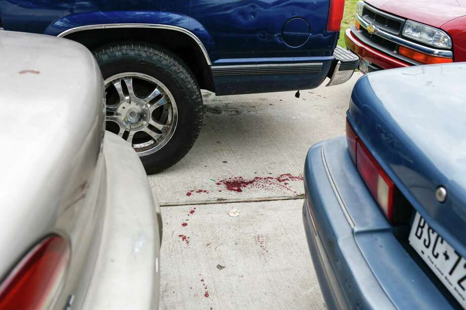 Blood splatter lies in the driveway of a home where two people were killed and at least 16 others wounded late Saturday when gunfire erupted at a house party in the Cypress area, authorities said. The shooting broke out about 11:15 p.m. in the 7300 block of Enchanted Creek Drive, near Fry and FM 529. Nov. 10, 2013 in Houston. Photo: Eric Kayne, For The Chronicle / Eric Kayne