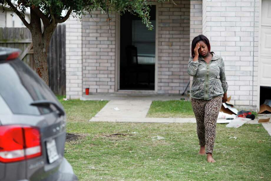 An unidentified woman walks away from the home where two people were killed and at least 16 others wounded late Saturday when gunfire erupted at a house party in the Cypress area, authorities said. The shooting broke out about 11:15 p.m. in the 7300 block of Enchanted Creek Drive, near Fry and FM 529. Nov. 10, 2013 in Houston. Photo: Eric Kayne, For The Chronicle / Eric Kayne