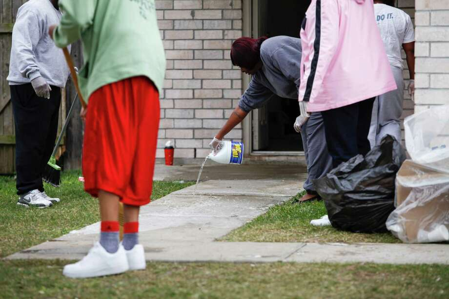 Tonya Grice uses hydrogen peroxide to clean the blood from the walkway of her sister's house where two people were killed and at least 16 others wounded late Saturday when gunfire erupted at a house party in the Cypress area, authorities said. The shooting broke out about 11:15 p.m. in the 7300 block of Enchanted Creek Drive, near Fry and FM 529. Nov. 10, 2013 in Houston. Photo: Eric Kayne, For The Chronicle / Eric Kayne