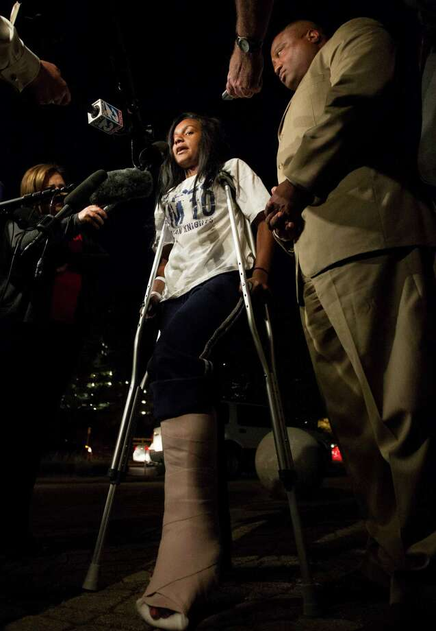 Quanell X stands with Brayiannia Young during a press conference outside Ben Taub hospital on Monday, Nov. 11, 2013, in Houston. Brayiannia was shot during a house party where two people were killed and 19 injured in the Cypress area on Saturday night.  Her brother, Willie Young, 21, was arrested and charged with deadly conduct  on Monday. A second suspect Randy Stewart, 18, was arrested and charged with aggravated assault.  She claims her brother could not have done the shooting. Photo: J. Patric Schneider, For The Chronicle / © 2013 Houston Chronicle