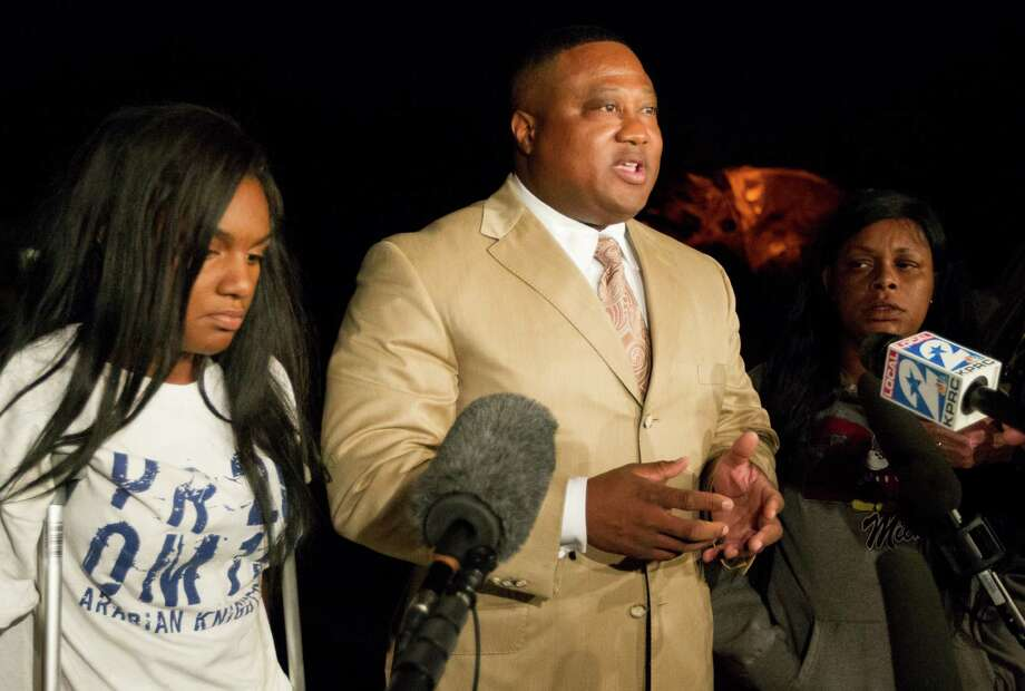 Quanell X stands with Brayiannia Young, left, and her mother Yolanda during a press conference outside Ben Taub hospital on Monday, Nov. 11, 2013, in Houston. Brayiannia was shot during a house party where two people were killed and 19 injured in the Cypress area on Saturday night.  Her brother, Willie Young, 21, was arrested and charged with deadly conduct  on Monday. A second suspect Randy Stewart, 18, was arrested and charged with aggravated assault.  She claims her brother could not have done the shooting. Photo: J. Patric Schneider, For The Chronicle / © 2013 Houston Chronicle