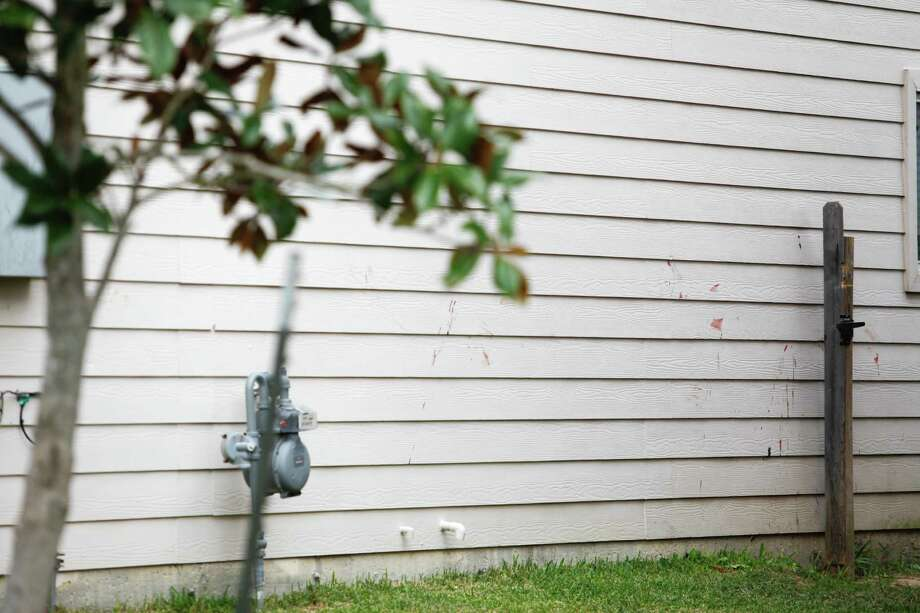 Blood stains lie on the side of a home where two people were killed and at least 16 others wounded late Saturday when gunfire erupted at a house party in the Cypress area, authorities said. The shooting broke out about 11:15 p.m. in the 7300 block of Enchanted Creek Drive, near Fry and FM 529. Nov. 10, 2013 in Houston. Photo: Eric Kayne, For The Chronicle / Eric Kayne