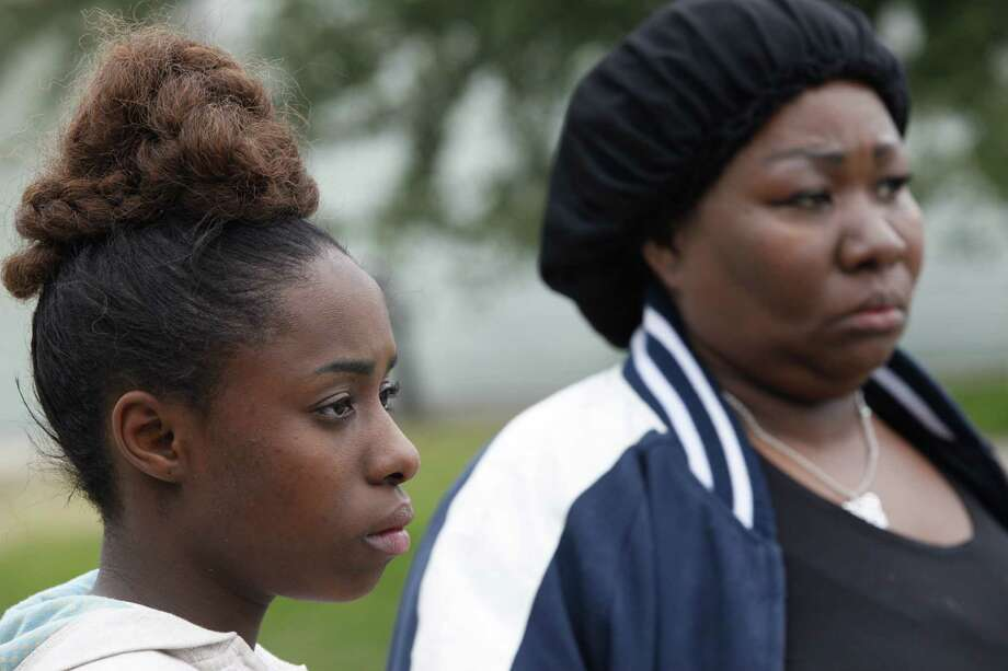 Shaniqua Brown, 17, left, who was at the party, and her mother Mary Brown stand in front of a home where two people were killed and at least 16 others wounded late Saturday when gunfire erupted at a house party in the Cypress area, authorities said. The shooting broke out about 11:15 p.m. in the 7300 block of Enchanted Creek Drive, near Fry and FM 529. Nov. 10, 2013 in Houston. Photo: Eric Kayne, For The Chronicle / Eric Kayne