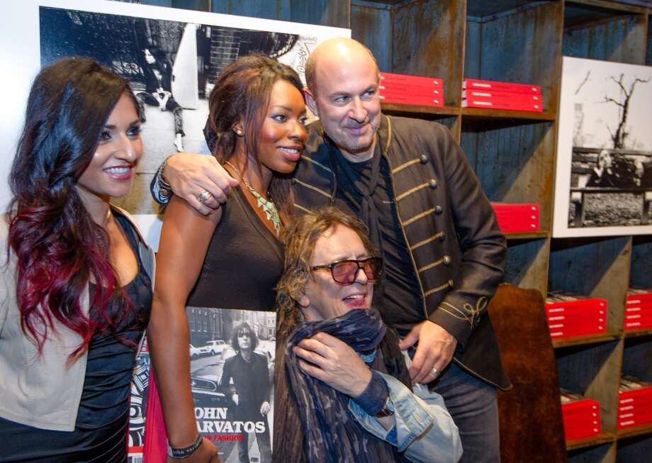 "Fashion designer John Varvatos (R) and photographer Mick Rock embrace fans at the launch of the book ""Rock In Fashion"" at John Varvatos on November 8, 2013 in San Francisco, California. Photo: Kimberly White, Getty Images For John Varvatos"