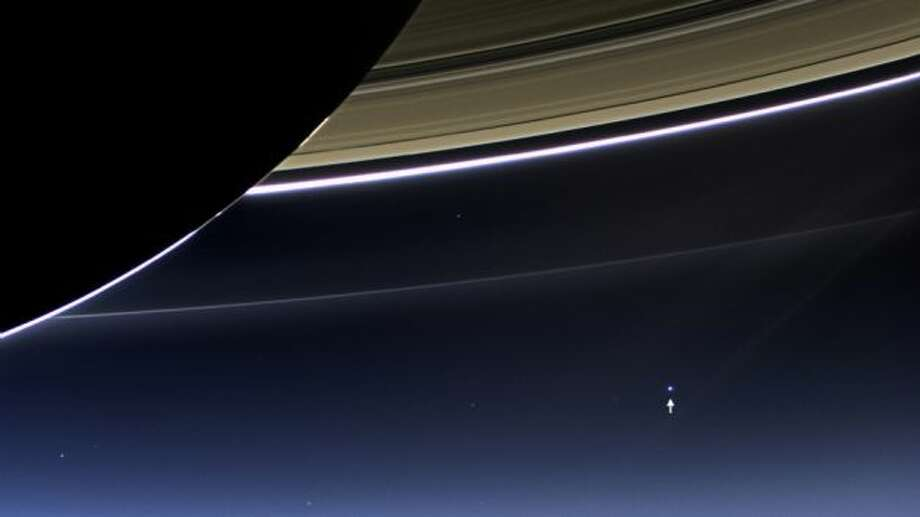 "This is the Earth from an earlier photo from Saturn:  In this rare image taken on July 19, 2013, the wide-angle camera on NASA's Cassini spacecraft has captured Saturn's rings and our planet Earth and its moon in the same frame. It is only one footprint in a mosaic of 33 footprints covering the entire Saturn ring system (including Saturn itself).   At each footprint, images were taken in different spectral filters for a total of 323 images: some were taken for scientific purposes and some to produce a natural color mosaic. This is the only wide-angle footprint that has the Earth-moon system in it. The dark side of Saturn, its bright limb, the main rings, the F ring, and the G and E rings are clearly seen; the limb of Saturn and the F ring are overexposed.   The ""breaks"" in the brightness of Saturn's limb are due to the shadows of the rings on the globe of Saturn, preventing sunlight from shining through the atmosphere in those regions. The E and G rings have been brightened for better visibility. Earth, which is 898 million miles (1.44 billion kilometers) away in this image, appears as a blue dot at center right; the moon can be seen as a fainter protrusion off its right side.   An arrow indicates their location in the annotated version. (The two are clearly seen as separate objects in the accompanying narrow angle frame: PIA14949.) The other bright dots nearby are stars. This is only the third time ever that Earth has been imaged from the outer solar system. Photo: NASA"