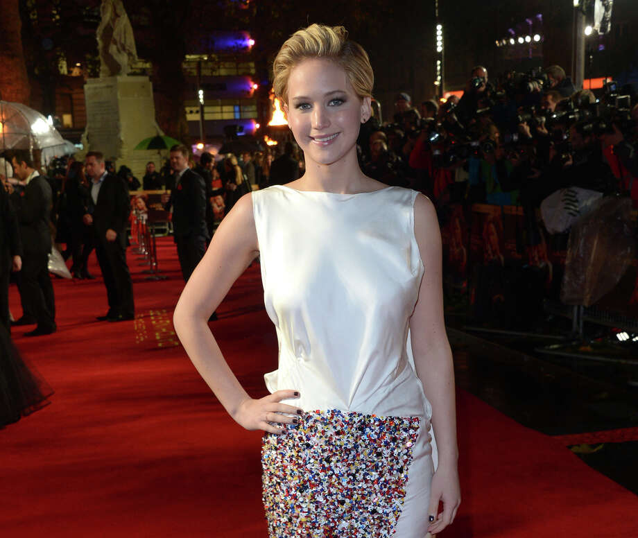 """American actress Jennifer Lawrence poses for photographers as she arrives on the red carpet for the World Premiere of """"The Hunger Games: Catching Fire,"""" on Monday Nov. 11,  2013, in Leicester Square, London. Lawrence will not only star in the upcoming film adaptation of Jeanette Walls' 2005 best-selling memoir """"The Glass Castle,"""" the project will also mark her first time as a producer.  A production date for the movie has not yet been set. (Photo by Jon Furniss/Invision/AP) ORG XMIT: CAET452 Photo: Jon Furniss / Invision"""