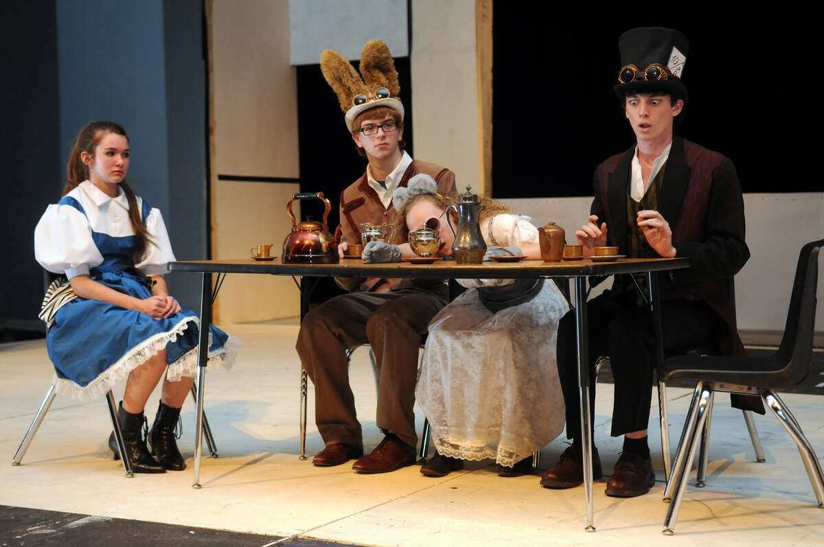 """Katie Pavlas, left, as Alice, Matthew Overturff, as the March Hare, Megan Todd, as the Dormouse, and Harvey Dunn, as the Mad Hatter, rehearse the """"Alice in Wonderland"""" tea party scene."""