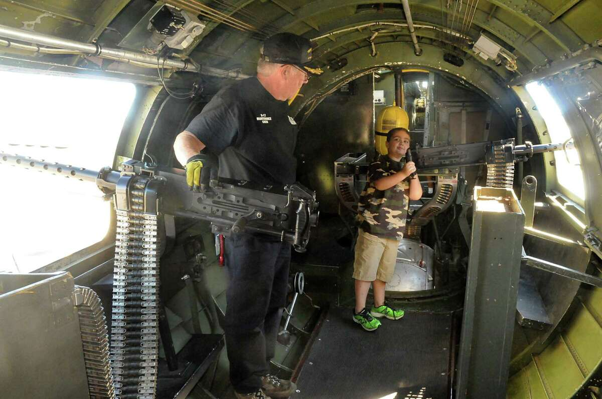"""Quinn Allen, 8, of Spring, """"operates"""" the machine gun on the B-17 under the watchful eyes of CAF member Dennis Kwiecien during a B-17 bomber tour."""