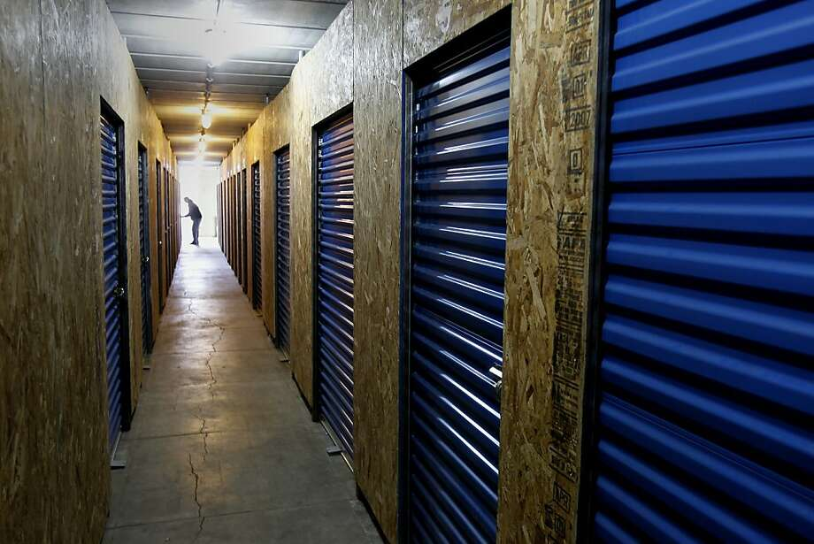 Presidio Wine Bunker, top, delivers a sense of safety, with clients storing their collections, middle, in a chilled setting. A photo of 1900-era artillery, above, is a reminder of the bunker's history. Photo: Brant Ward, The Chronicle