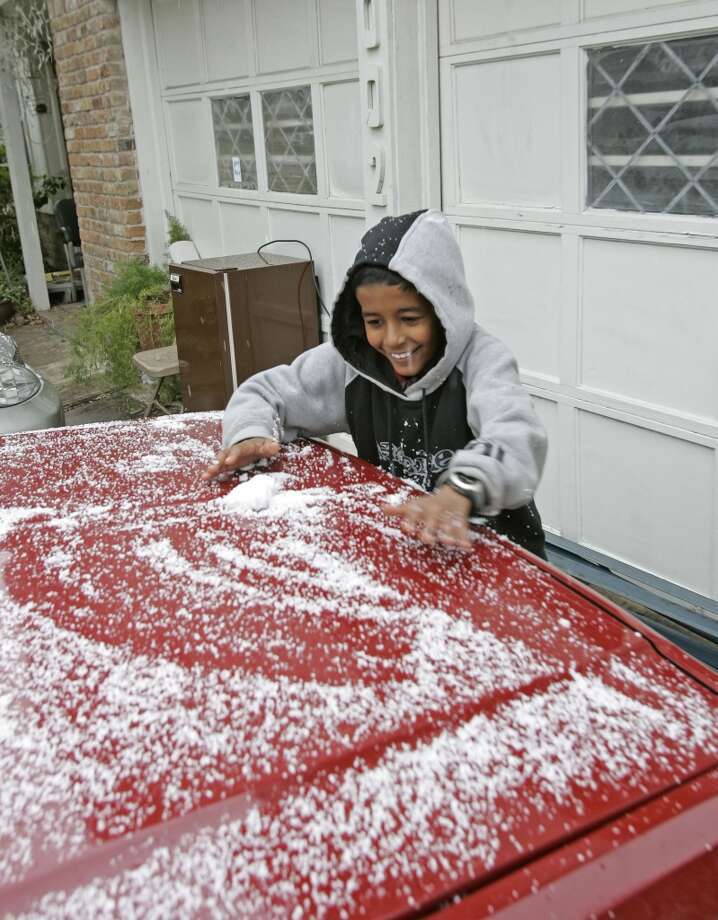 Deepak Guatam, 10, experiences the thrill of gathering the makings for his first snowball in west Houston on Christmas Day in 2004. Photo: CRAIG H. HARTLEY, FOR THE CHRONICLE