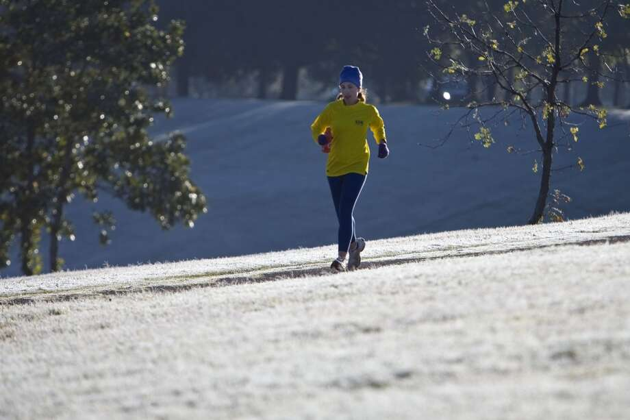 A jogger run on a trail past the snow and frost covered grass in Buffalo Bayou Park Saturday, Dec. 5, 2009, in Houston. Photo: James Nielsen, Houston Chronicle