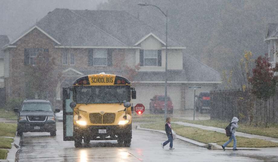 Kaufman Elementary School students in the Conroe ISD leave their school bus home as it snows in Spring in December 2004. Photo: Brett Coomer, Houston Chronicle
