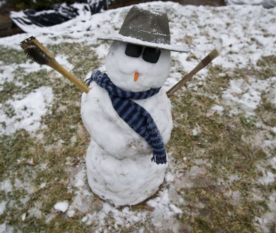 "Pictured is a snowman named ""Briskit"" built by 10 year olds Chloe Gentry and Sara Wells as snowfalls Friday, Dec. 4, 2009, in Houston. Photo: James Nielsen, Houston Chronicle"