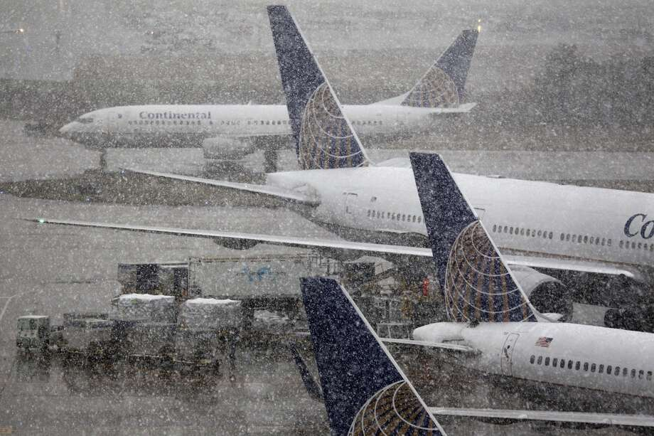 Continental Airlines jets are seen through the falling snow at Bush Intercontinental Airport on Friday afternoon, Dec. 4, 2009, in Houston.   Airlines cancelled about 100 flights at Bush and Hobby airports, said Frank Haley, deputy director of operations and public safety for the Houston Airport System.  There have been some flight delays, because all departing planes are stopping at de-icing stations before proceeding onto the runway for takeoff. De-icing has been underway since about 5 a.m. and will continue as long as Houston experiences freezing rain or snow. Photo: Smiley N. Pool, Houston Chronicle
