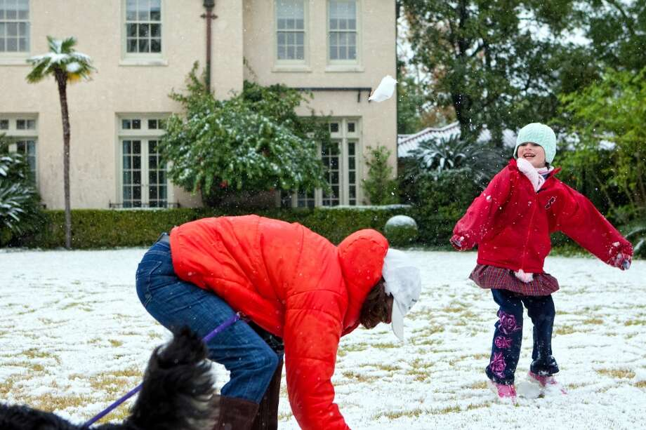 Kelley Trammell and her daughter Sophie, 6, play in the freshly fallen snow in front of their River Oaks home, Friday, Dec. 4, 2009 in Houston, Texas. With the earliest recorded snowfall in Houston history, Kelley's two children were released early from their school, St. Johns. Photo: TODD SPOTH, For The Chronicle