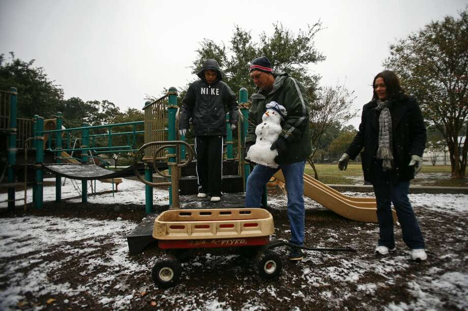 "Eric Moore, 11, (left) gets help from his parents, Terry and Sylvie, to transport the snowman he and his brother built from Cherryhurst Park to their home during the snowfall Friday, Dec. 4, 2009, in Houston. ""The hardest part was collecting the snow before it melted,"" Eric said.  ""It's pretty cool; we got out of school early, it's snowing and now we have a snowman named Buddy."" Photo: Michael Paulsen, Houston Chronicle"