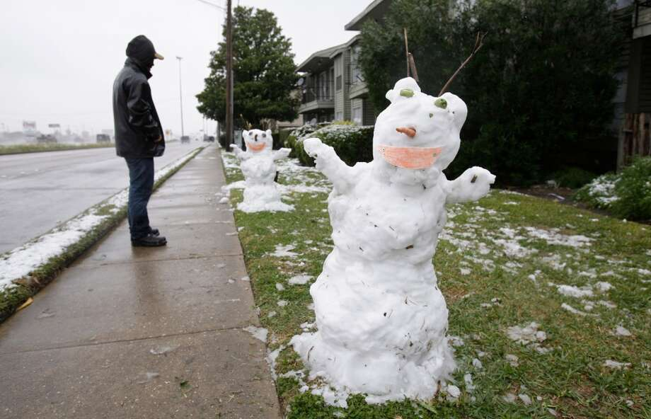 Jairo Cruz looks at the two snowmen he and his family spent three hours building outside their apartment at The Oxford, 10909 Gulf Freeway,  Friday, Dec. 4, 2009, in Houston. Photo: Melissa Phillip, Houston Chronicle
