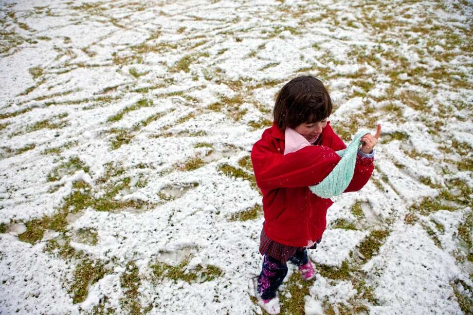Sophie Trammell, age 6, stuffs her hat full of freshly fallen snow in front of her River Oaks home, Friday, Dec. 4, 2009 in Houston, Texas. With the earliest recorded snowfall in Houston Sophie was released early from her school, St. Johns. Photo: TODD SPOTH, For The Chronicle