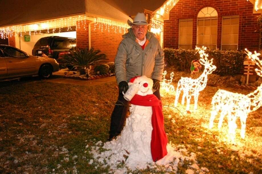Joe Villarreal offers the snowman his family built in the front yard a drink after the snow storm in 2004. Photo: Jorge De La Garza, Houston Chronicle Files / handout email