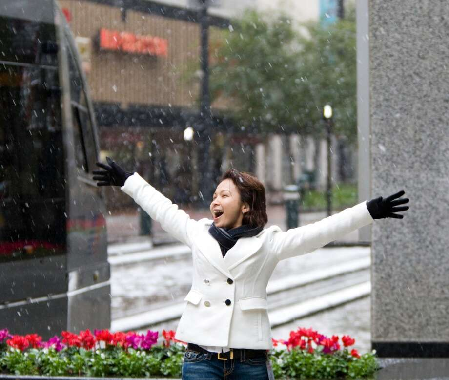 Amy Ta poses as her friends take her picture during heavy snow fall Friday, Dec. 4, 2009, in downtown Houston. Photo: Nick De La Torre, Houston Chronicle