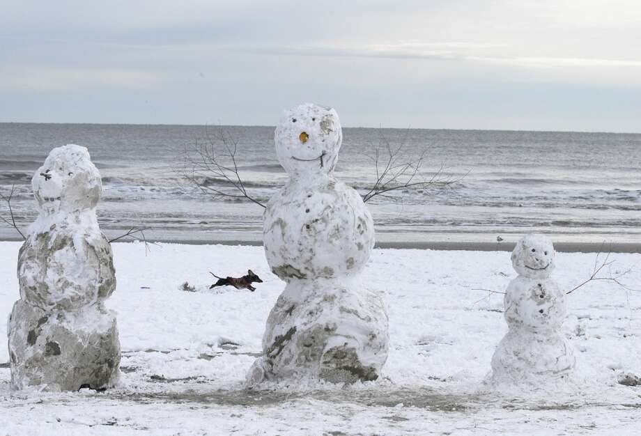 A Dachschund runs behind three snowmen on the beach on Saturday morning. Galveston island saw a white Christmas with a record snow fall as residents estimated five inches on the ground in 2004. Photo: Carlos Javier Sanchez, Houston Chronicle