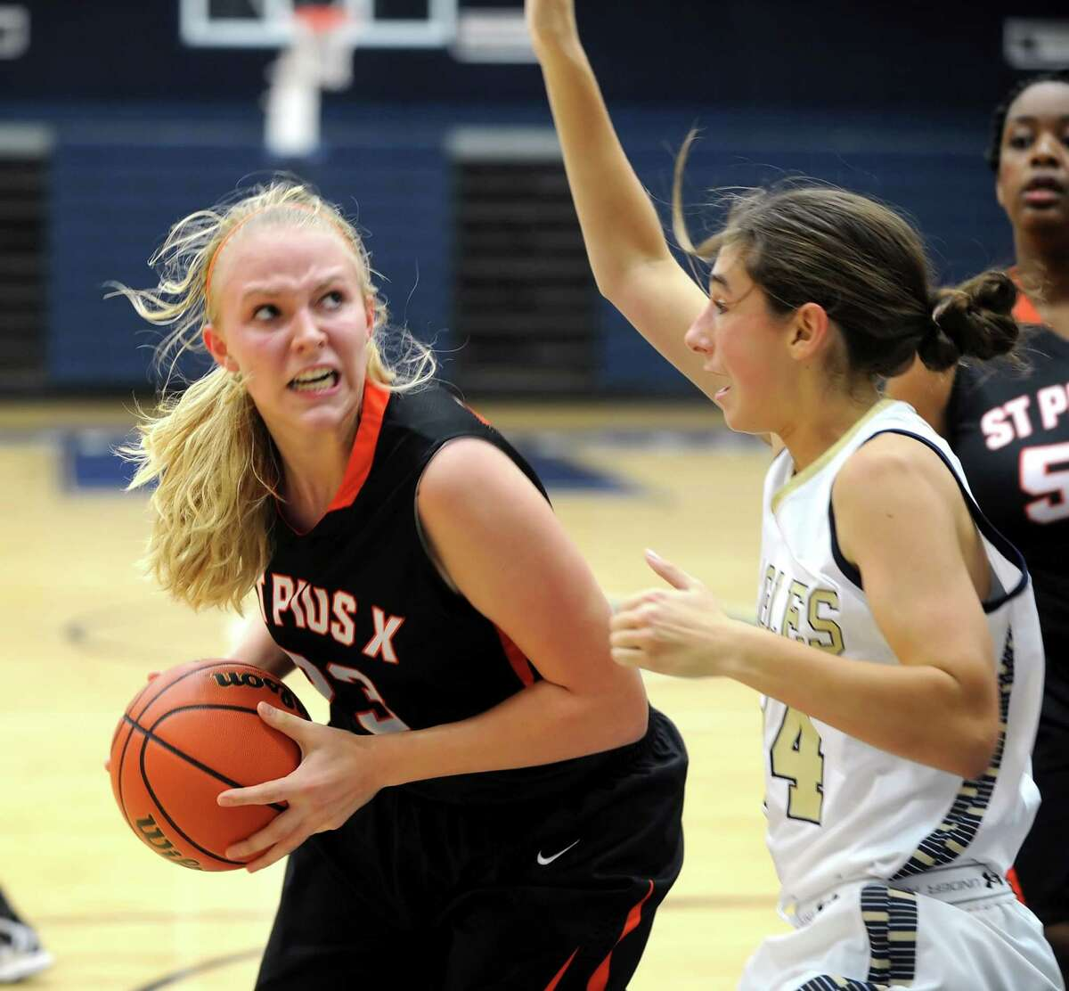 St. Pius visited second Baptist High School for a girls basketball game. Second Baptist won the game, 52-48. Left, St. Pius front court player Laura Daulton (23) is pressured under the basket by Second Baptist defender Taylor Kollmorgen (24).