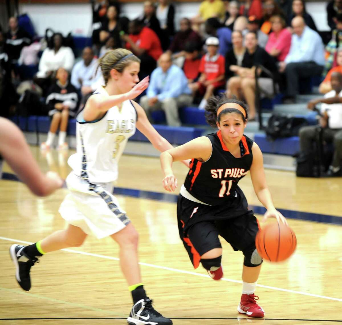 St. Pius visited second Baptist High School for a girls basketball game. Second Baptist won the game, 52-48. Right, Scarlet Rodriguez (11) of St. Pius, drives toward the basket and is being guarded by Second Baptist's Michelle Howard (3).