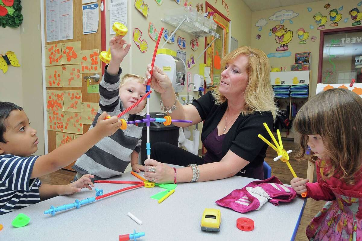 At The Goddard School in Cypress, Rayyan Mohammed, left, and Brendan Seda Smith play with a toy as school director Cathy Robinson oversees their reactions during a new-toy testing event.
