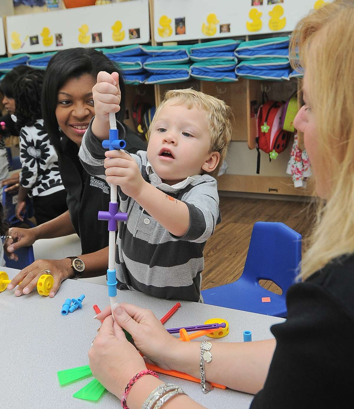 At The Goddard School in Cypress, Melannie Lewis (cq) watches as Brendan Seda Smith (cq) plays with a lego-like toy with Cathy Robinson at right Friday 11/01/13.