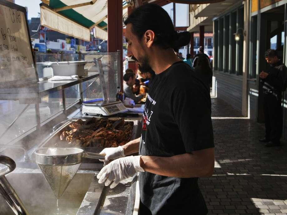 Omar Garcia cooks fresh crab at the sidewalk cafe at Tarantino's. Photo: Raphael Kluzniok, The Chronicle