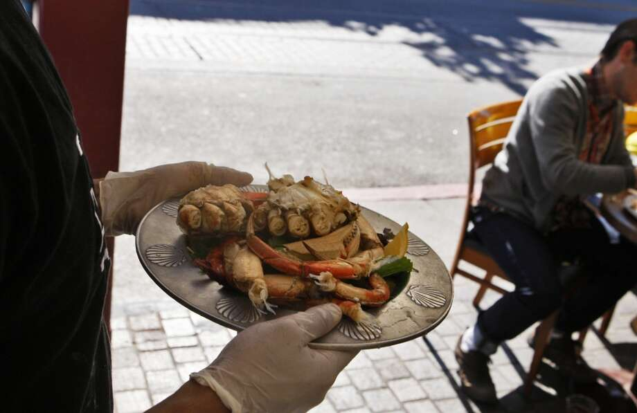 Omar Garcia carries a plate of crab to a waiting table at the sidewalk cafe at Tarantino's. Photo: Raphael Kluzniok, The Chronicle