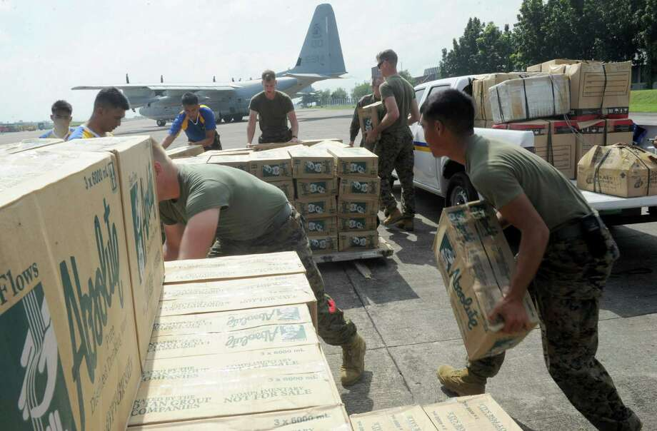 "Philippine and US military personnel load relief goods for Tacloban on board a US C-130 plane for victims of Super Typhoon Haiyan  that hit the Cental Philippines, at a military base in Manila on November 11, 2013.  Australia boosted its funding for relief efforts in the Philippines to 9.38 million USD with Foreign Minister Julie Bishop describing the unfolding tragedy as ""absolutely devastating"".     AFP PHOTO / Jay DIRECTOJAY DIRECTO/AFP/Getty Images ORG XMIT: 187517569 Photo: JAY DIRECTO / AFP"