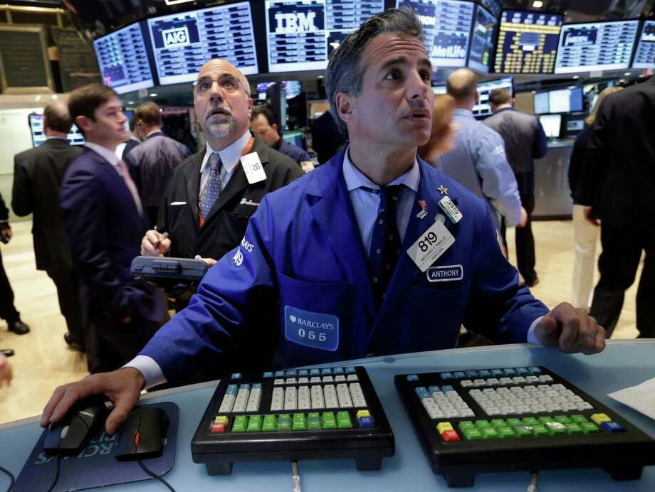 Trader John Liotti, left, and specialist Anthony Rinaldi work on the floor of the New York Stock Exchange Tuesday, Nov. 12, 2013. Stocks are mostly lower in early trading on Wall Street, led by a decline in utilities stocks. (AP Photo/Richard Drew) ORG XMIT: NYRD102 Photo: Richard Drew / AP