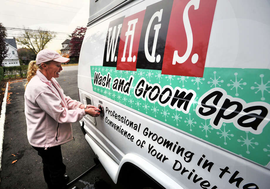 Janine McCormick, owner of Wash and Groom Spa, a mobile dog grooming service, refills the water tank in her van outside her home in Stamford, Conn., on Tuesday, Nov. 12, 2013. McCormick trims hair and nails as well as bathes her client's dogs. Photo: Jason Rearick / Stamford Advocate