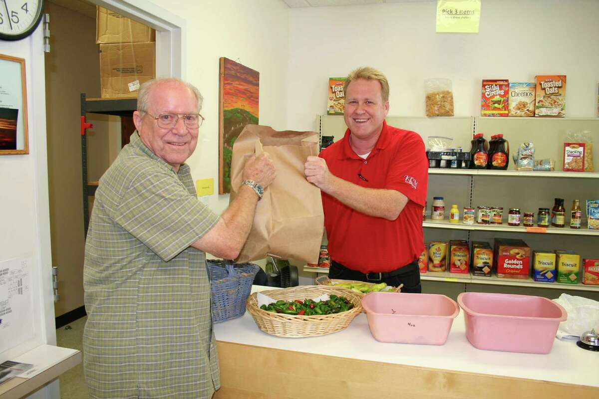 Curtis Casburn, left, is a volunteer at the Katy Christian Ministries food pantry, and Derrick Espey is the director of the food pantry. Clients of the ministries receive a bag of groceries.Curtis Casburn, left, is a volunteer at the Katy Christian Ministries food pantry, and Derrick Espey is the director of the food pantry. Clients of the ministries receive a bag of groceries.