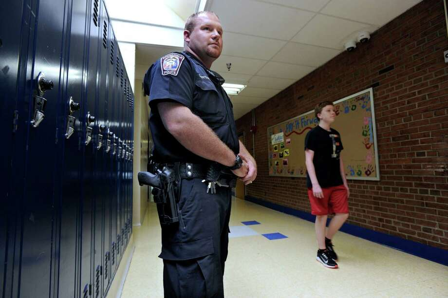 In this file photo, Brookfield Police School Resource Officer Devin Quintard, assigned to Brookfield High School, in Brookfield, Conn, watches the halls. Photo: Carol Kaliff / The News-Times