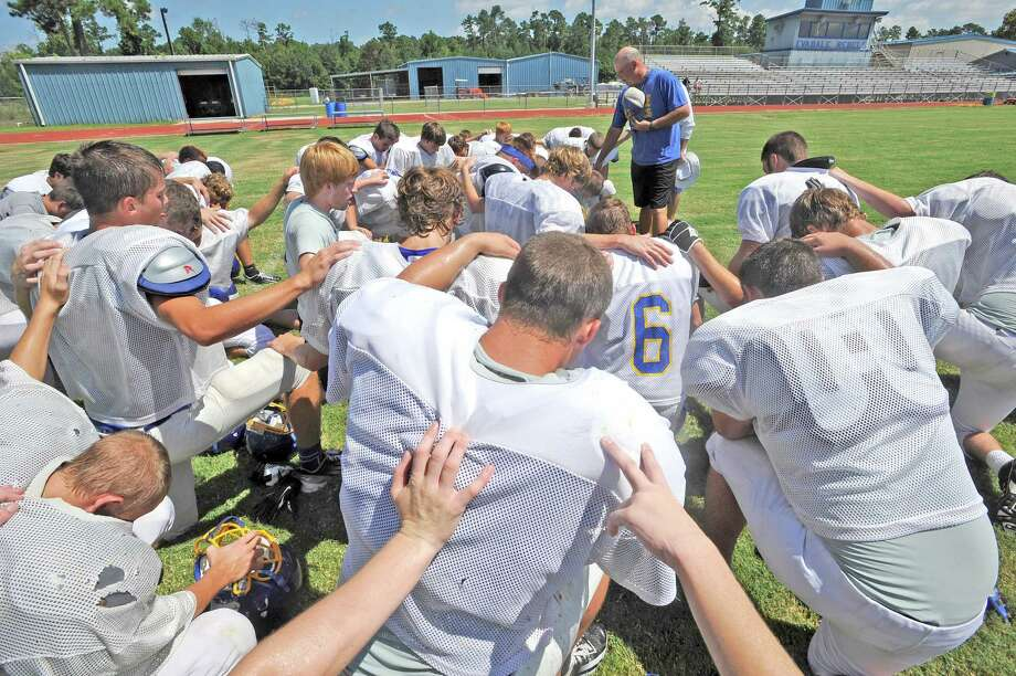 Evadale head coach Mark Williams (right) prays with his players at the end of practice. Enterprise file photo