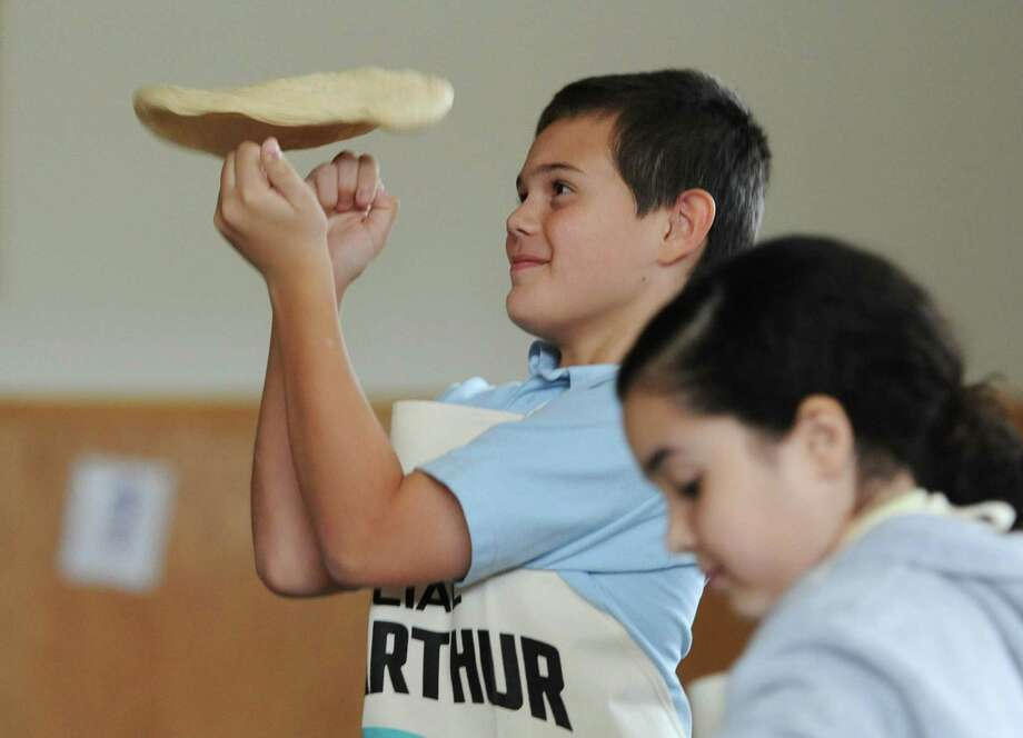 Sixth-grader Robert Yastremski demonstrates to his classmates how to toss pizza dough at the Life Skills Bread Baking Program, presented by King Arthur Flour, at St. Joseph School in Danbury, Conn. on Tuesday, Nov. 12, 2013.  The cross-curricular program taught 100 fourth- through seventh-grade students how to bake bread products from scratch through hands-on demonstrations.  The students were given ingredients and encouraged to bake at home and bring back a loaf of bread to donate to charity. Photo: Tyler Sizemore / The News-Times