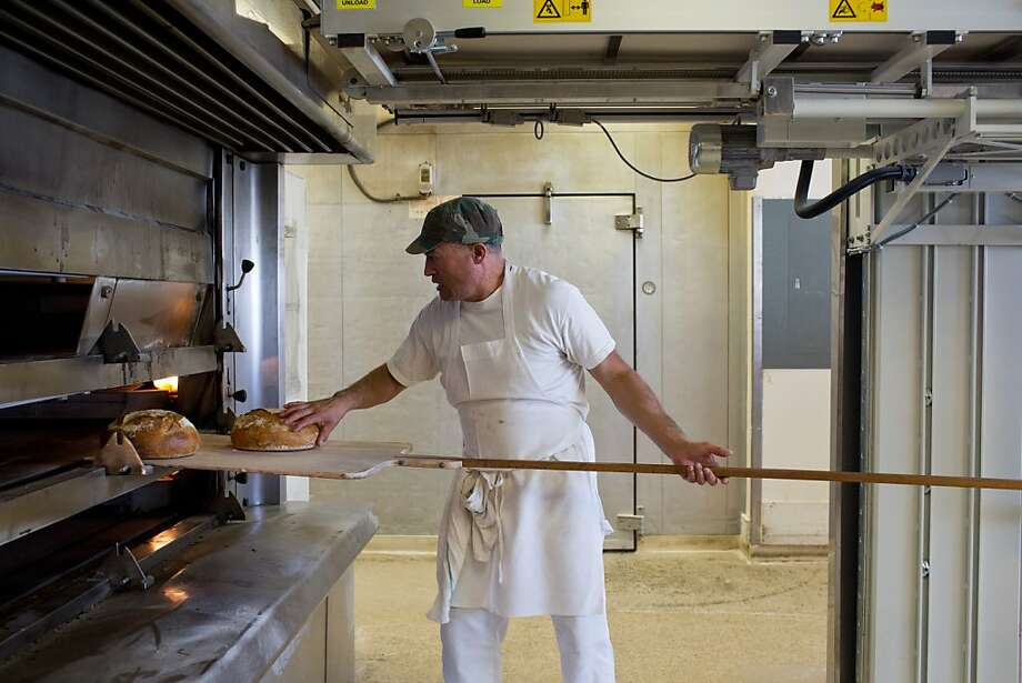 Javier Randon works an oven as he bakes bread at Gayle's Bakery & Rosticceria in Capitola. A conveyor-style oven loader places the loaves deep inside the deck ovens, and cake layers are loaded onto a head-high rack and rotated in a room-size baking chamber. The bakery was only 800 square feet when it opened in 1978. Photo: Jason Henry, Special To The Chronicle